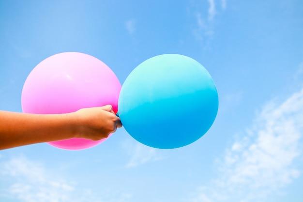 少年の手は青とピンクの風船を持っています。背景は明るい空です。ハッピー Premium写真