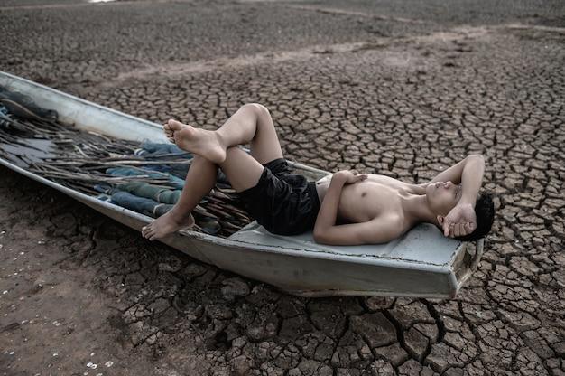 Мальчик спал на рыбацкой лодке и положил руки на лоб на сухой пол, глобальное потепление Бесплатные Фотографии