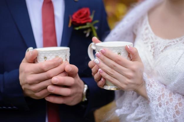 新郎新婦はお茶のマグを持っています。 Premium写真