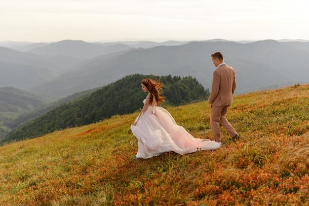 Жених и невеста идут рядом друг с другом. закат солнца. свадебное фото на фоне осенних гор. сильный ветер раздувает волосы и платье. Premium Фотографии