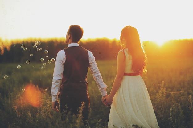 Жених и невеста держатся за руки и гуляют по парку. Premium Фотографии