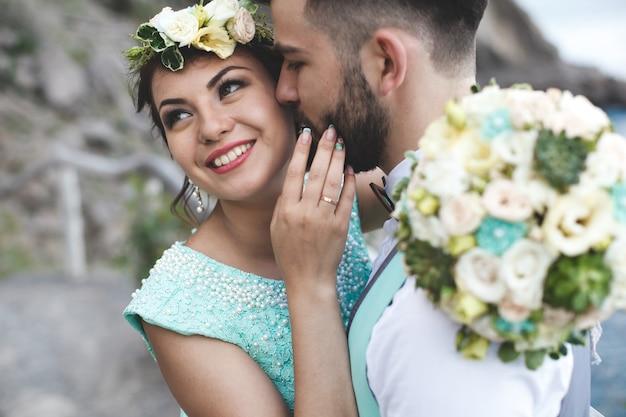 Жених и невеста на природе в горах у воды. костюм и платье цвета тиффани. поцеловать и обнять. невеста смеется. Premium Фотографии