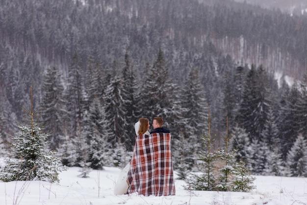 Жених и невеста стоят на фоне гор и обнимаются под ковриком, чтобы согреться. зимняя свадьба Premium Фотографии