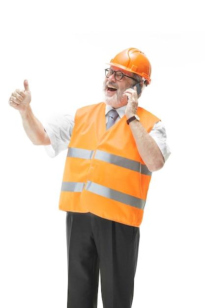 건설 조끼에 작성기 및 뭔가에 대해 휴대 전화에 말하는 주황색 헬멧. 무료 사진