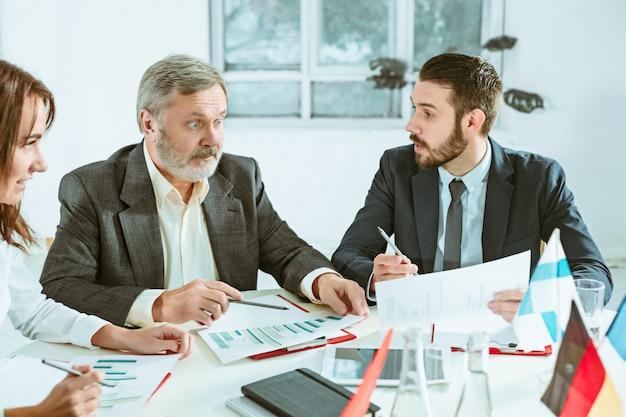Деловые люди работают вместе за столом. Бесплатные Фотографии