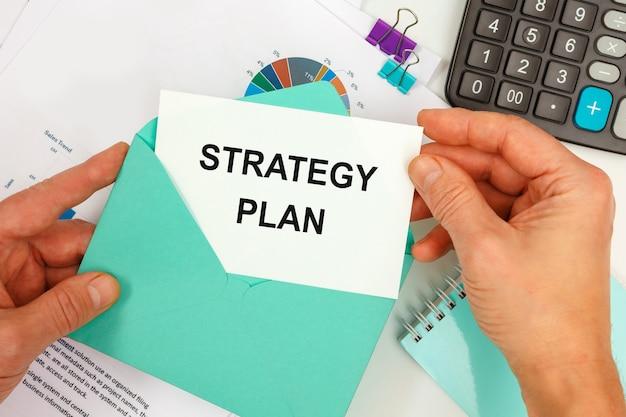 사업가는 사무실 책상 배경에 Strategy Plan이라는 텍스트가있는 봉투에서 카드를 꺼냅니다. 프리미엄 사진