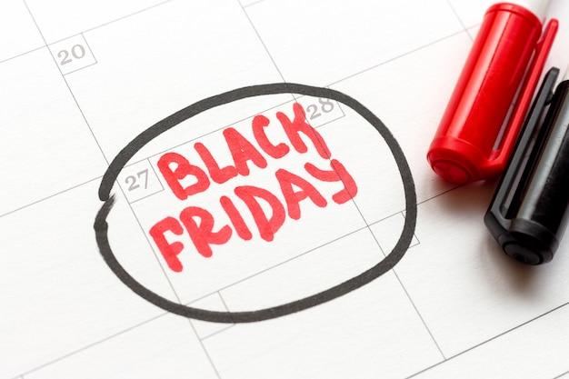В календаре есть черная пятница и два черных и красных маркера. Premium Фотографии