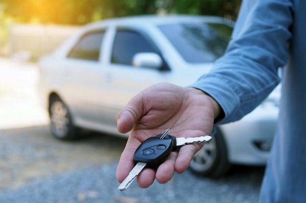 車の所有者は購入者に車の鍵を渡しています。中古車販売 Premium写真