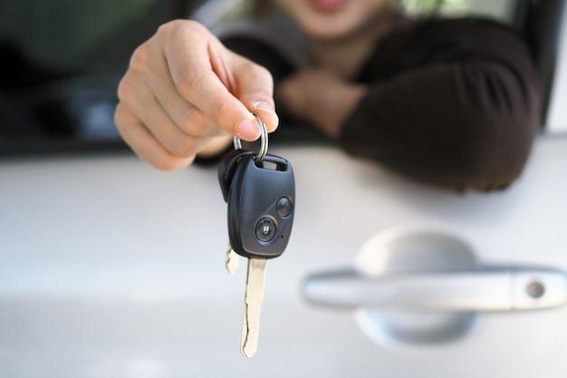 車の所有者はバイヤーに車のキーを立てています Premium写真
