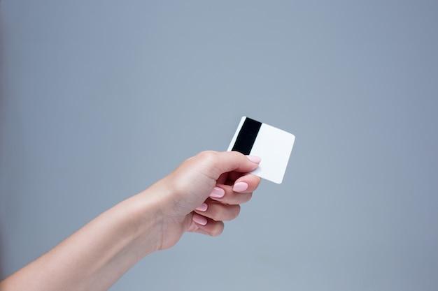 女性の手のカードは灰色の背景に 無料写真