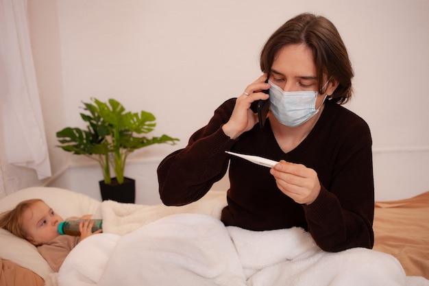 Ребенок болен, отец в маске проверяет температуру дочери. Premium Фотографии