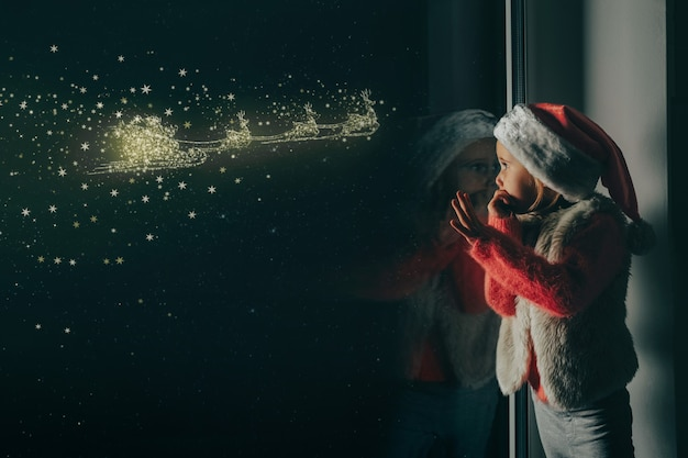 子供はイエス・キリストのクリスマスに窓の外を見ます。 Premium写真