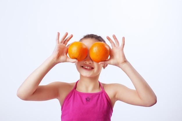 Ребенок с апельсинами. Premium Фотографии