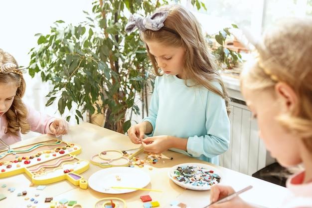 子供と誕生日の飾り。食べ物、ケーキ、ドリンク、パーティーガジェットを備えたテーブルセッティングの男の子と女の子。 無料写真
