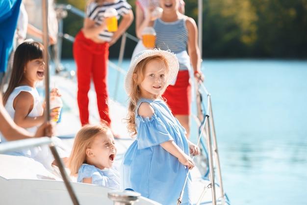 오렌지 주스를 마시는 바다 요트의 보드에 아이들. 푸른 하늘 야외에 대 한 청소년 또는 어린이 소녀. 화려한 옷. 키즈 패션, 화창한 여름, 강 및 휴일 개념. 무료 사진