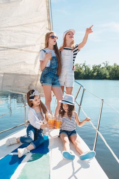 Дети на борту морской яхты пьют апельсиновый сок Бесплатные Фотографии