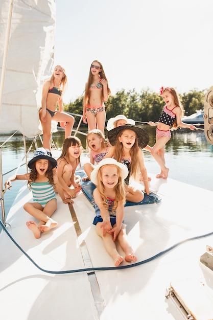 바다 요트에 타고있는 아이들. 야외 십대 또는 어린이 소녀. 화려한 옷. 키즈 패션, 화창한 여름, 강 및 휴일 개념. 무료 사진