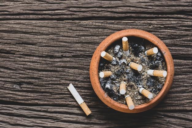 鍋のタバコの尻は、古い木の床に置かれています。 Premium写真