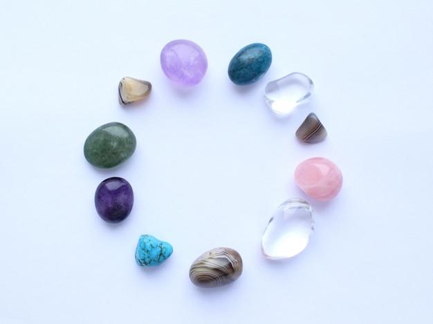 Круг выложен натуральными минералами. полудрагоценные камни разного цвета, необработанные и обработанные. аметист, розовый кварц, агат, апатит, авантюрин на белой стене. Premium Фотографии