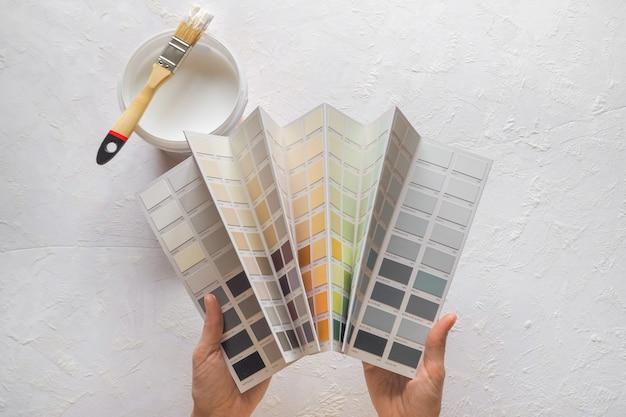 Цвет эмали в руках. выбор цвета краски для стен. Premium Фотографии