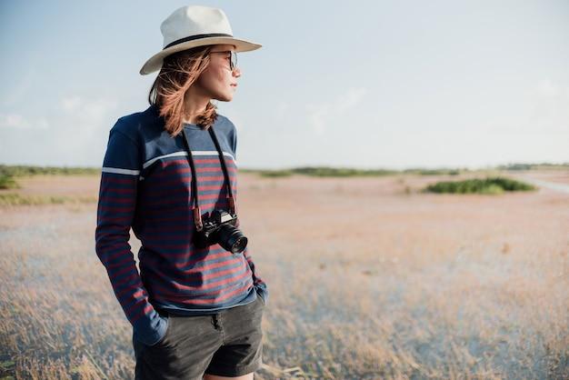 首にカメラを持ってアジアの女性を撮影する観光客のコンセプト手スリ横を見る Premium写真