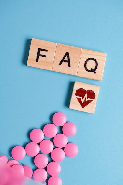 Понятие о базовых, общих вопросах лекарств, таблеток для сердца. розовые таблички рядом с деревянным квадратом и буквами - faq. Premium Фотографии