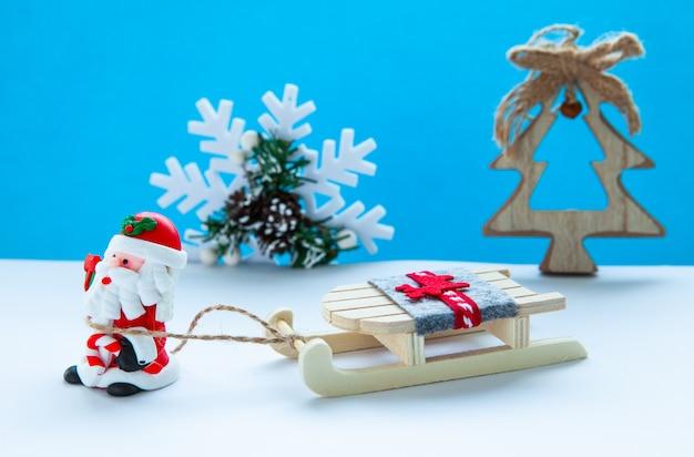 正月休暇のコンセプト。ライトブルーの背景には、sleighとサンタクロース Premium写真