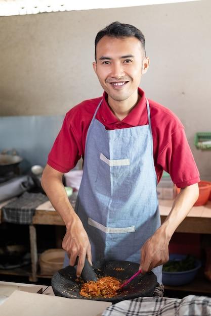料理人は、キッチンで調理するために乳鉢でスパイスを広げながら微笑んだ。 Premium写真