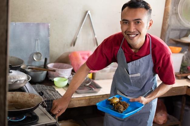 屋台で客のためにおかずを揚げるためにストーブをつけたとき、料理人は微笑んだ。 Premium写真