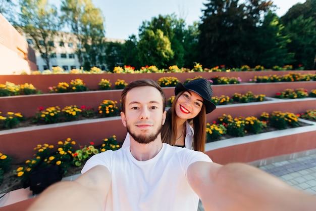 愛するカップルは、マルチレベルの花壇の背景にセフィーを作ります Premium写真