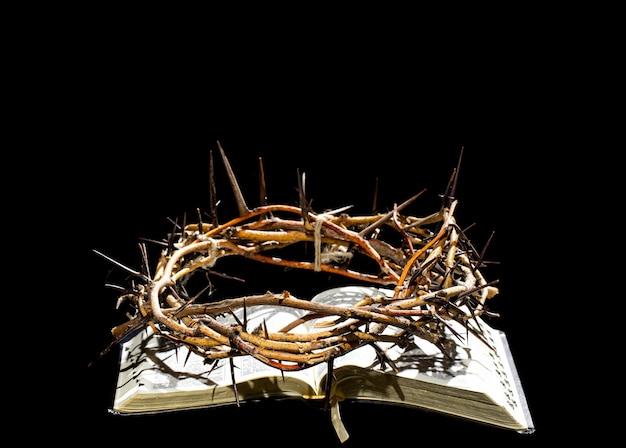 いばらの冠は暗闇の中で聖書の本の上にあります。聖週間の概念とイエスのはりつけ。 Premium写真