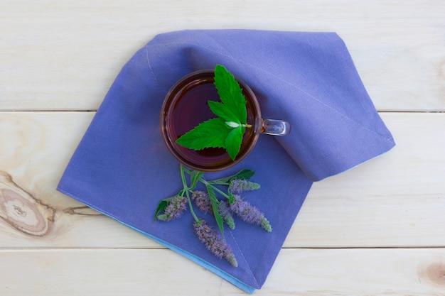 木製のテーブルにミントとミントの花の枝と紅茶のカップ Premium写真