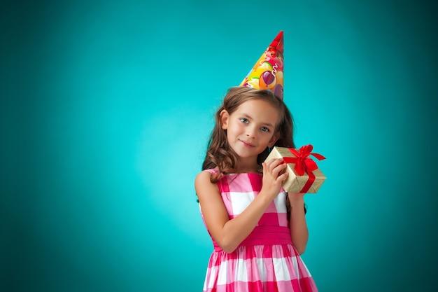 青の背景にギフトとお祝いキャップとかわいい陽気な女の子 無料写真