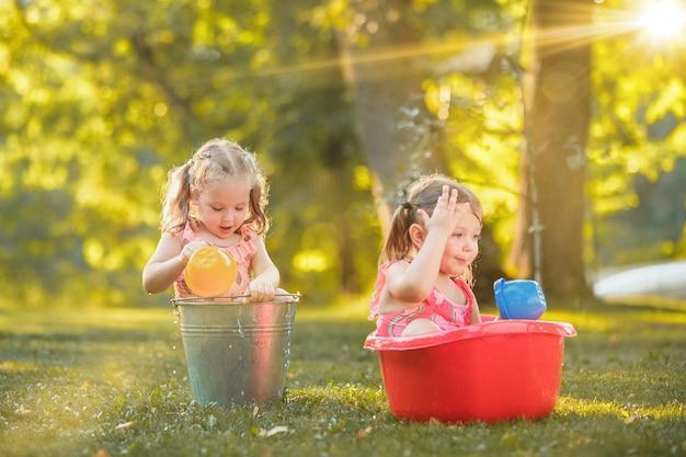 Милые маленькие белокурые девочки играют с брызгами воды на поле летом Бесплатные Фотографии