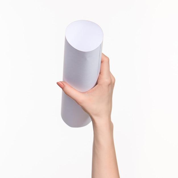白い壁に女性の手でシリンダー 無料写真