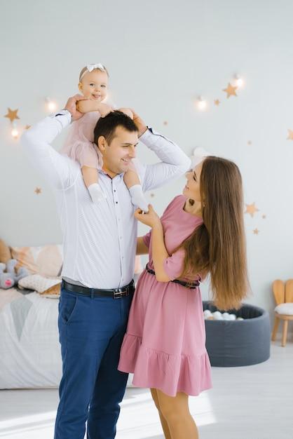 娘は微笑み、父親の首に転がります。幸せなママが待機しています Premium写真