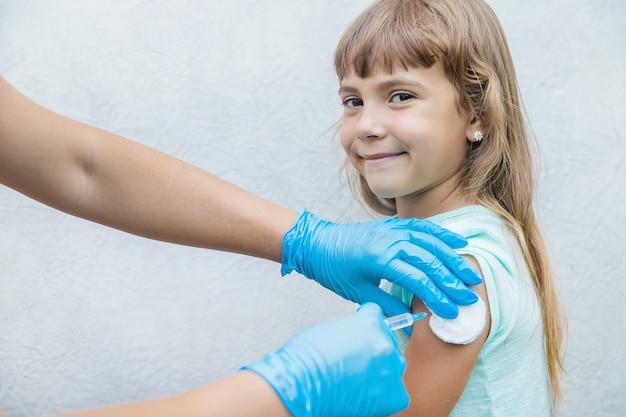 医者は子供に腕に注射をします Premium写真