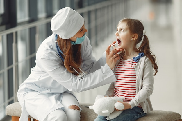 Доктор в маске щадит горло антисептиком для ребенка Бесплатные Фотографии