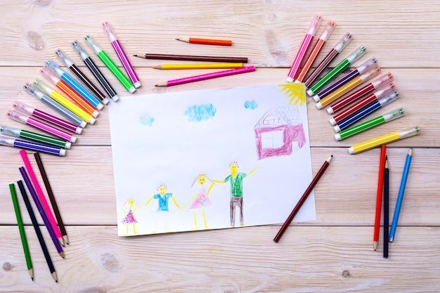図面は、子供が色付きのマーカーと鉛筆を使用して作成しました。家族、両親、子供、家の子供の絵。幸せな家族。子どもの絵 Premium写真