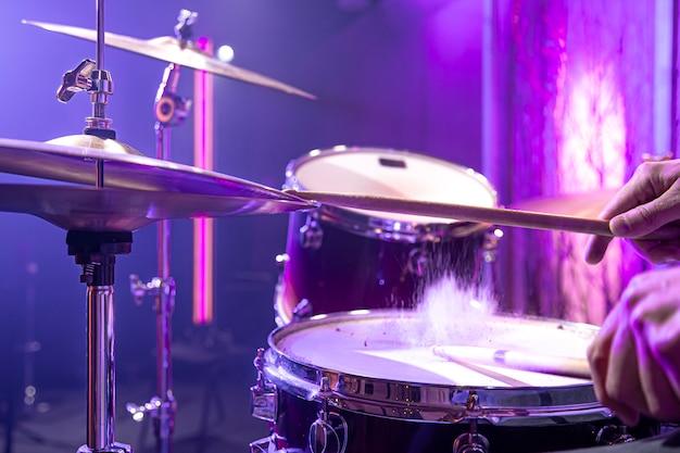 드러머는 아름다운 배경 가까이에 스튜디오에서 드럼 키트를 재생합니다. 무료 사진