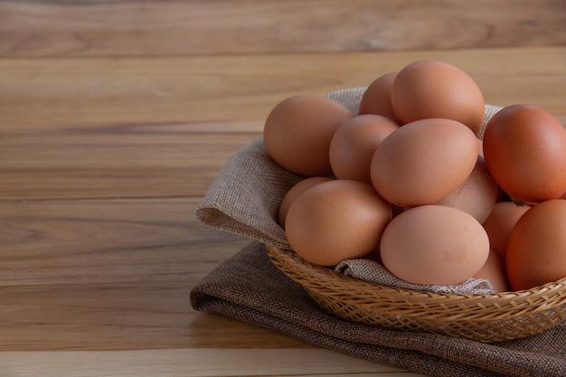 バスケットの卵は木の床に置かれます。 無料写真