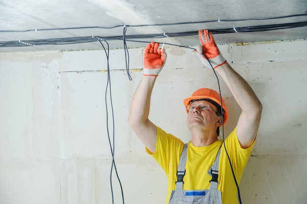 Электрик крепит к потолку электрические кабели. Premium Фотографии