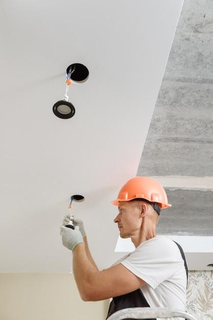 전기 기사가 천장에 Led 조명을 설치하고 있습니다. 프리미엄 사진