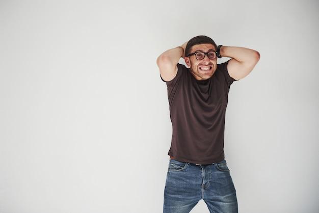 カジュアルな服装とメガネを着た感情的な人は、取り返しのつかない間違いがなされているように見えます 無料写真