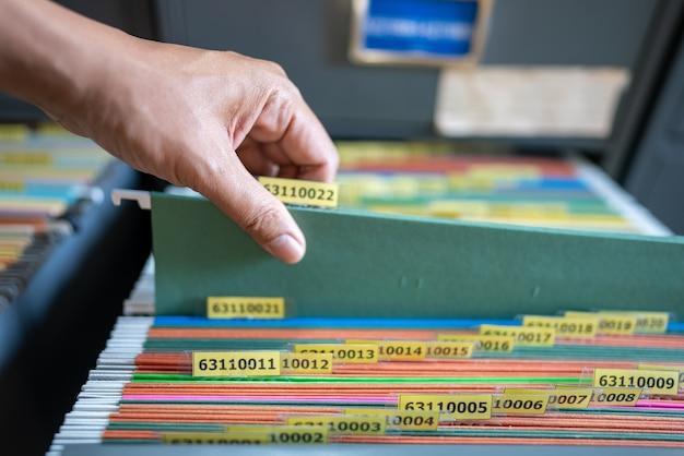 従業員の手は、ファイリングキャビネットで書類を探していました。 Premium写真