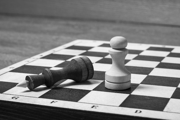 Конец шахматной партии, белая пешка победила темного ферзя. Premium Фотографии