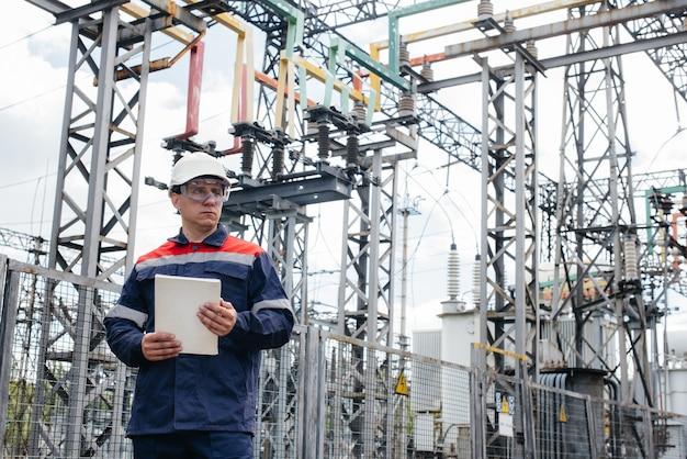 Инженер-энергетик осматривает оборудование подстанции. Premium Фотографии