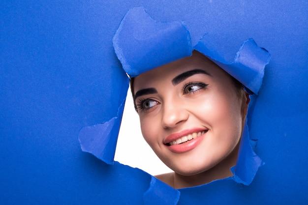 밝은 화장과 푹신한 푸른 입술을 가진 젊은 아름 다운 여자의 얼굴은 파란 종이에 구멍으로 동료. 무료 사진