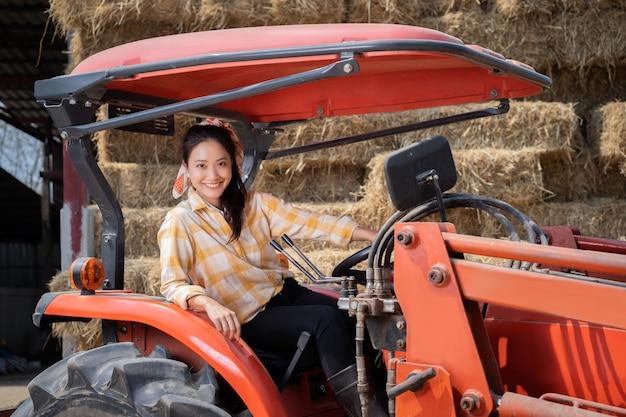 農夫、彼女はトラクターと一緒です。彼の後ろには牛に餌をやるわらの山があった 無料写真
