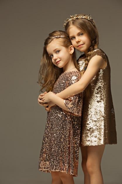 ゴールドのドレスの若い美しい10代の女の子のファッションの肖像画。美しさ、ファッション、輝き、メイクアップ、そして輝くコンセプト。白人モデル 無料写真